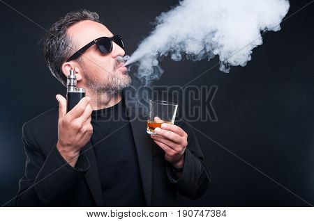 Rich Man Exhaling Vapor From An Electronic Cigarette