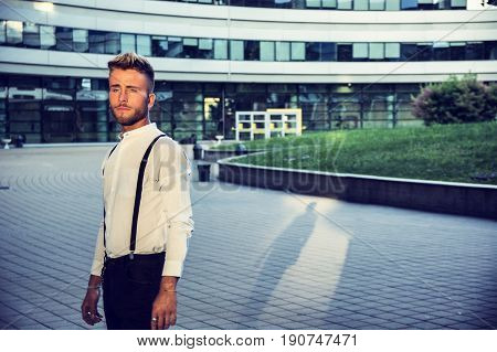 Blond Young Man Next to Modern Building in City, Wearing White Shirt and Suspenders, Standing