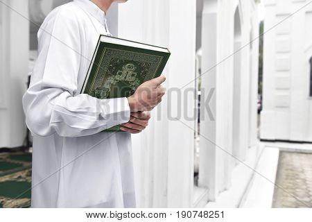 Muslim Man Hands Holding The Koran