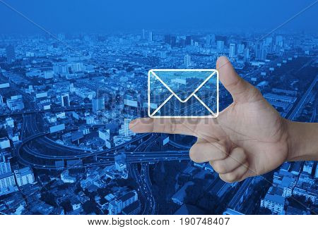 Mail icon on finger over modern city tower street and expressway Contact us concept