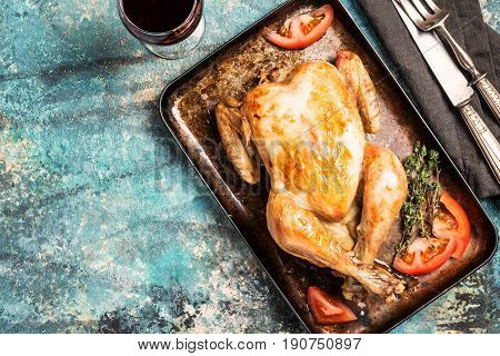 Roasted whole chicken with a golden crust with vegetables on a blue background, top view