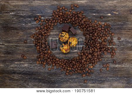 Beautiful coffee beans and candies on a wooden table