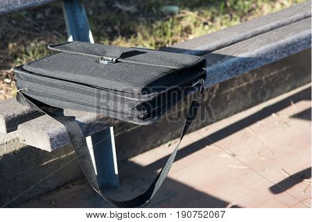 Abandoned black computer bag over a bench