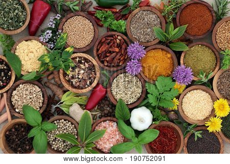 Herb and spice sampler in wooden bowls and loose forming a background, high in vitamins and antioxidants.