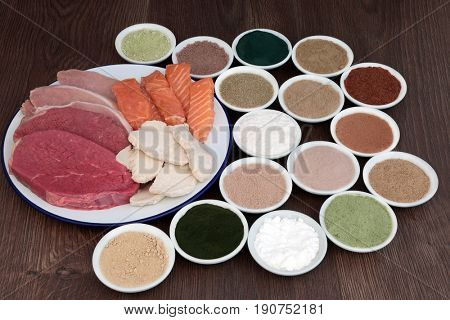 High protein food for body builders of lean steak, pork, chicken, salmon with dietary supplement powders on oak background.
