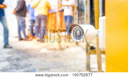 Surveillance camera and security concept - Close up Surveillance cctv camera on gate of construction site people with flare light effect and copyspace
