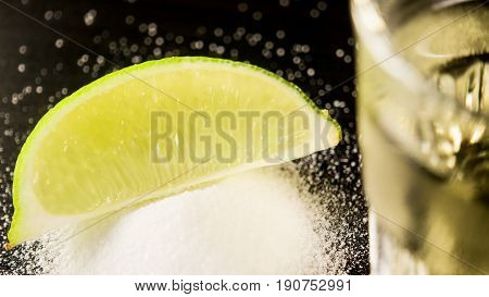 Lime slice on salt in focus and next to a shot of tequila is out of focus