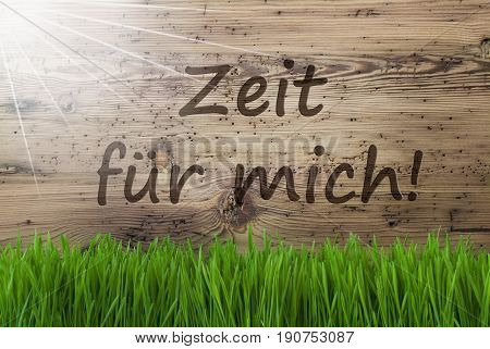 German Text Zeit Fuer Mich Means Time For Me. Spring Season Greeting Card. Sunny Aged Wooden Background With Gras.