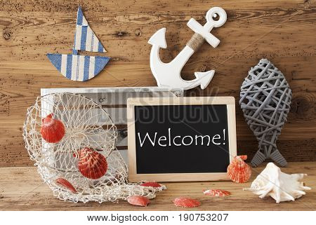 Blackboard With Nautical Summer Decoration And Wooden Background. English Text Welcome. Fish, Anchor, Shells And Fishnet For Maritime Contex.