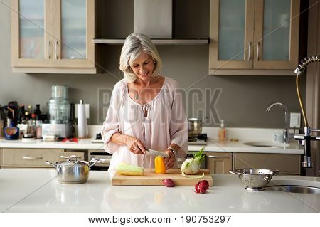 Older Woman Preparing Food For A Meal In Kitchen