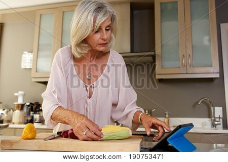 Older Woman In Kitchen Searching For Recipe On Digital Tablet