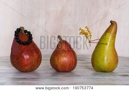 Conceptual composition with the pears. Pear with a bouquet of flowers. Still life with pears. Three pears