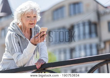 Glad attractive old lady is listening to music through her headphones and looking to her smartphone. She is standing by metal fence. Copy space in right side