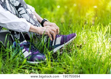 Close up of legs of old lady sitting on yoga mat laying on grass. She is tying shoelaces on her sneakers. Focus on sport shoes