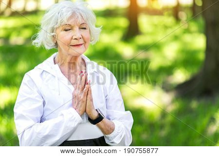 Waist up portrait of restful elderly lady performing yoga position among summer forest trees. She is closing her eyes and putting hands together as prayer