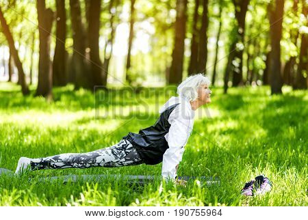 Profile of happy old woman standing in plank position among park trees. She is training on sport mat barefoot and smiling