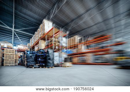 Large hangar warehouse industrial and logistics companies. Warehousing on the floor and called the high shelves. Toning the image. Motion blur effect.