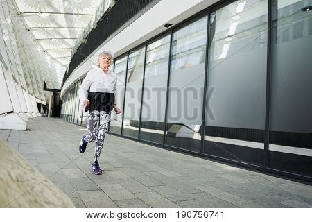Concentrated elderly woman is jogging nearby up-to-date construction. Copy space in right side