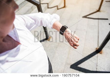 Close up of hand of old serious woman looking at her smart watch on wrist. She is standing on stairs with metal rails. Focus on tracker
