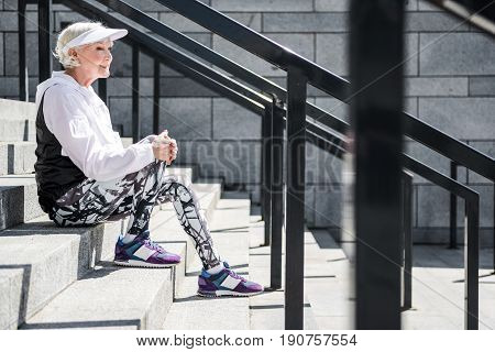 Profile of old happy lady sitting on stone stairs with handrails. She is having rest time. Copy space in right side