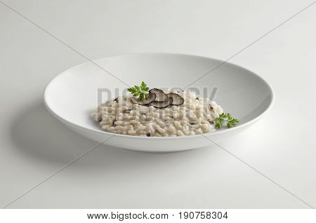 Bowl of risotto with truffle isolated on white table