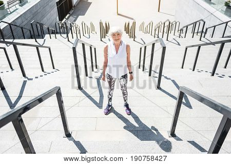 Portrait of happy old woman standing on big city stairs with metal handrails. She is going to train cardio drill. Top view