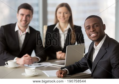 Attractive afro american cheerful businessman looking at camera sitting at desk, young african manager leading meeting for subordinates at background, business consulting, mixed-race team leadership