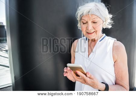 Happy old woman is communicating via smartphone beside metal wall. She is writing sms and smiling. Copy space in left side