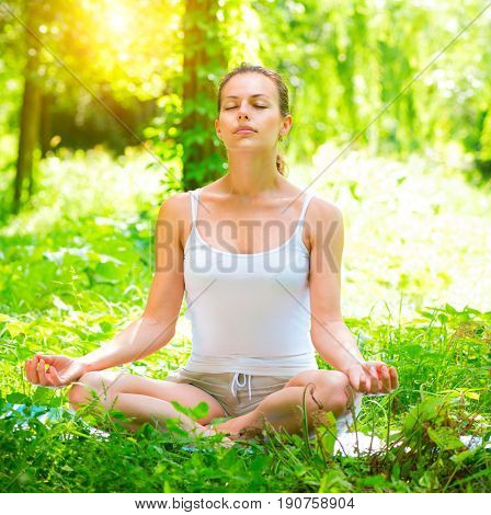 Yoga. Young Woman doing Yoga Exercises Outdoors. Beautiful Girl practicing yoga in the park. Relaxation, meditation. Zen. Healthy lifestyle concept