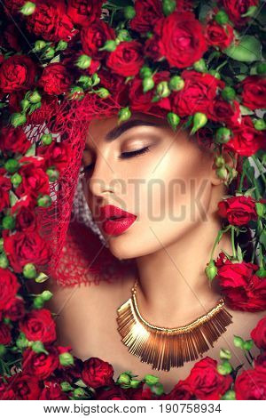 Beauty model girl with red roses flower wreath and fashion make up. Flowers Hair Style. Beautiful Lady with Blooming flowers on head. Nature Hairstyle. Holiday Fashion Makeup with red lipstick