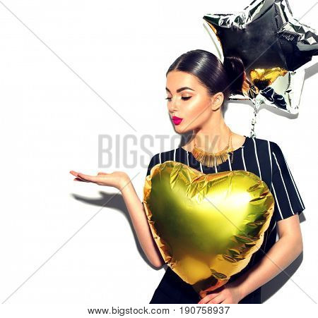 Beautiful fashion model party girl with colorful heart and star shaped balloons posing at studio isolated on white. Beauty sexy woman celebrating, showing empty copy space on open hand palm for text