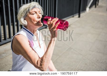 Thirsty old lady is sitting near railing of city establishment and drinking water from special sport bottle. She is resting after exercise. Focus on bottle