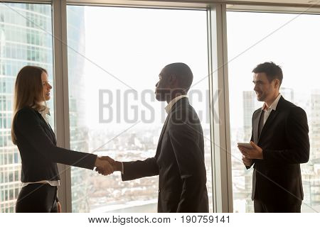 Businessman and businesswoman handshaking standing at big window in modern office, multicultural partners start meeting, get acquainted, nice to meet you, welcoming and ready to negotiate, join team