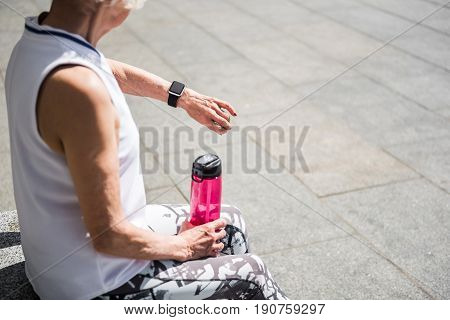 Close up of body and hands of old lady sitting on granitical block outside. She is holding bottle of water in her hand and looking on smart watch on her other hand. Copy space in right side