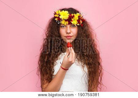 Horizontal studio shot of young woman wearing chaplet made with flowers and holding a strawberry.