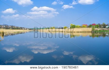 Ukrainian spring landscape with river named Sura and blue cloudy sky.