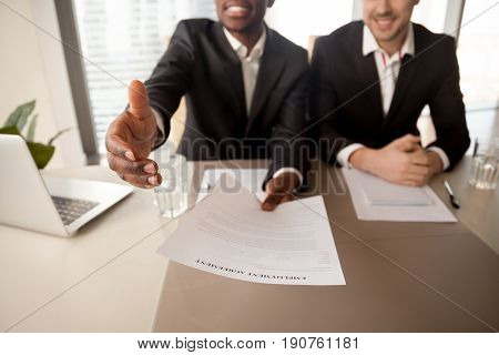 Close up of black businessman offering job, reaching out employment agreement to successful applicant, labor contract of work, extending hand for handshake, hiring new employee, getting job