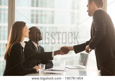 Friendly black and white recruiters sitting at office desk shaking hands with applicant just arrived for interview, diverse hr managers greeting candidate, nice to meet you and good first impression
