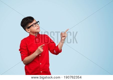 Boy in red shirt and glasses pointing with both hands up on blue background.
