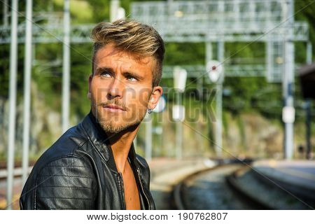 Attractive blond young man standing on railroad tracks, wearing only black leather jacket, looking away