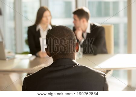 Nervous african-american applicant waiting for result after job interview, hr managers making decision at background, black businessman patiently awaits for claim complaint consideration, back view