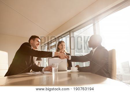 Cheerful black and white partners handshaking over office desk at multi-ethnic meeting with businesswoman, multiracial businessmen handshaking starting finishing negotiations, making profitable deal