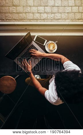 Top view of young man sitting at coffee shop and working on laptop. Vertical overhead shot of male using laptop at cafe.