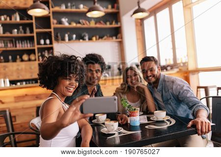 Group Of Friends At Restaurant Taking Selfie