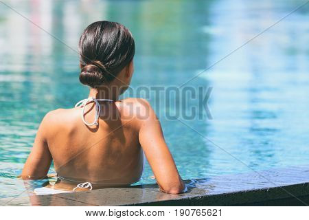 Swimming pool wellness spa woman relaxation at luxury travel resort relaxing in water at hotel vacation getaway.