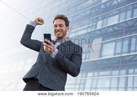 Success winner business man winning on cellphone app. Cheering businessman looking at smartphone online gaming challenge or work deal.