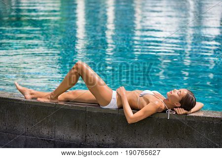 Luxury travel woman relaxing sunbathing by infinity pool at vacation resort, summer holidays. Suntan bikini Asian girl lying down at hotel.