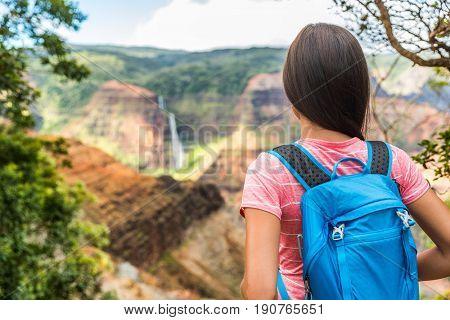 Hawaii hiking girl looking at Kauai waterfall. Woman hiker at Waipoo falls, Waimea Canyon, Hawaii. Kauai travel. Backpacker on hike trail in hawaiian forest overlooking mountains. Nature wanderlust.