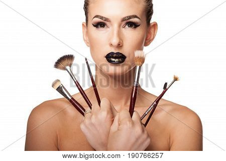 Woman holding makeup brushes in hands on white background in studio photo. Beauty image. Professional artistic makeup