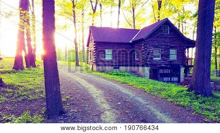 A log cabin out in the country with sun glare.